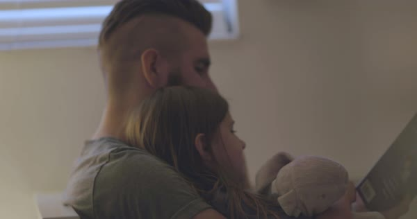 Hand-held shot of a man and his daughter reading a picture book Royalty-free stock video