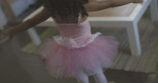 Hand-held shot of a little girl in a tutu dancing ballet in a living room Royalty-free stock video