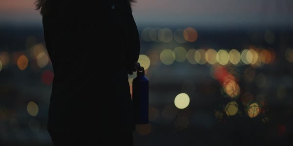 Hand-held shot of a woman enjoying view of a city while holding a water bottle Royalty-free stock video