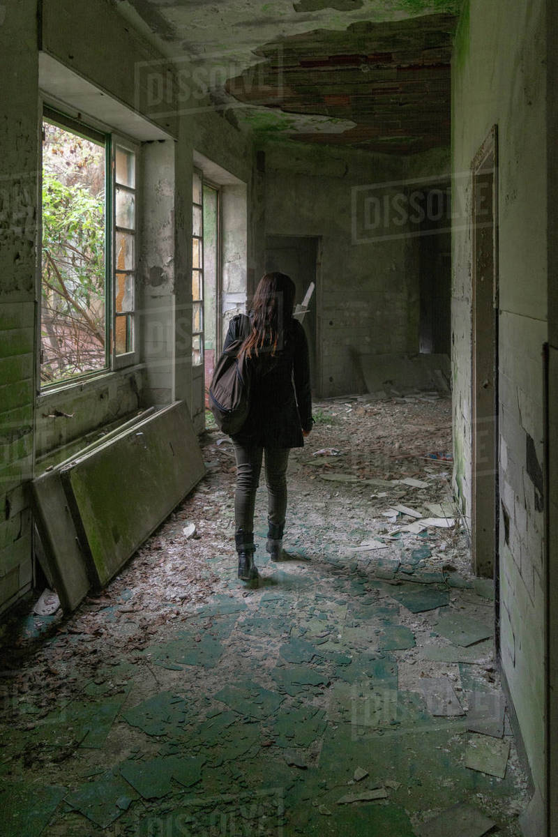 Girl walk in old abandoned building in decay hallway to explore it from back walking with backpack  Royalty-free stock photo