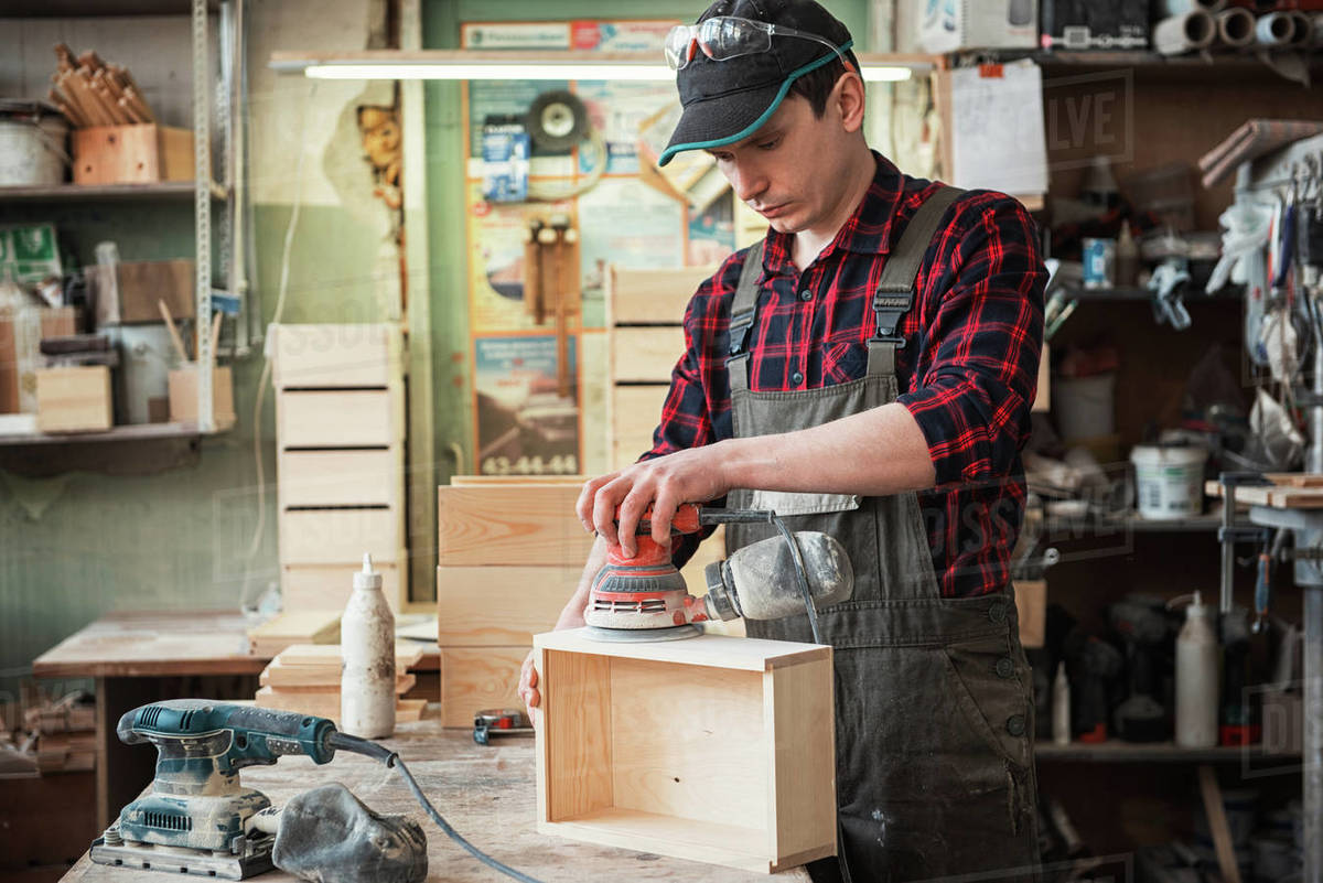 Worker grinds the wood box of angular grinding machine Royalty-free stock photo