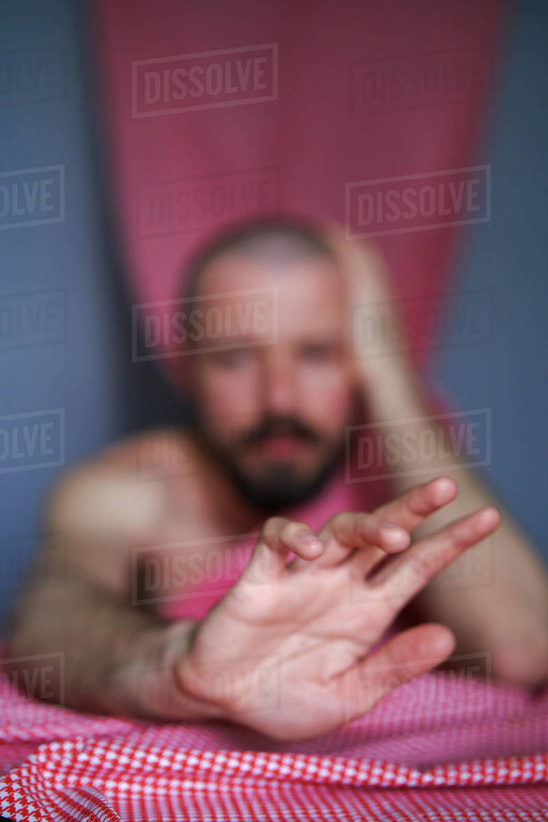 Unrecognisable man reaches for the camera, sitting at the table Royalty-free stock photo
