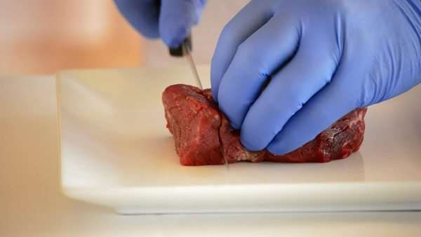 Hands of chef or professional chef cutting red veal or beef Royalty-free stock video