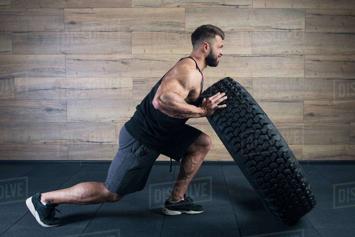 A strong man in a black tank top and grey shorts with a beard tries to push a tire in a gym. A muscular shredded guy doing a crossfit workout. A fellow with tattoos doing hardcore exercise.  Royalty-free stock photo