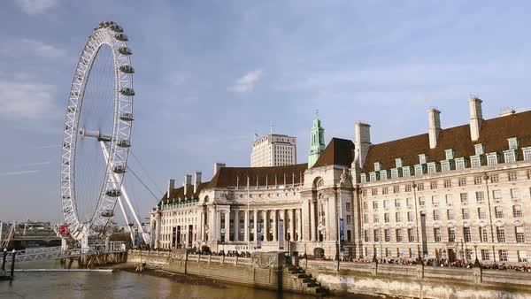 County Hall and the London Eye on the South Bank of the Thames opposite Westminster, London, UK. Rights-managed stock video