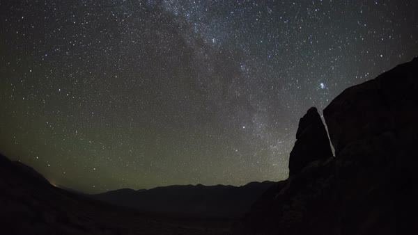 Milky Way and dawn in a desert. Time-lapse footage of the Milky Way in the night sky above a rocky skyline in a desert before dawn. Rights-managed stock video