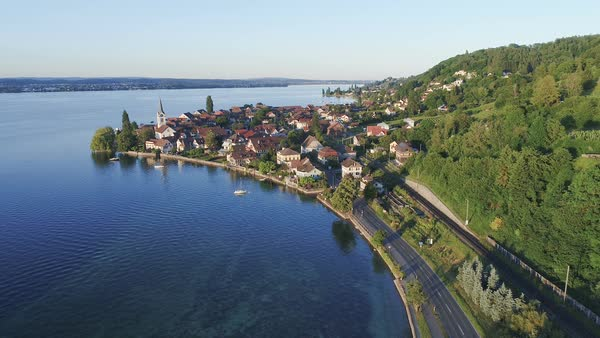 Aerial drone footage with view of the lower section of Lake Constance, showing the bay and church at Berlingen, Thurgau, Switzerland. Rights-managed stock video
