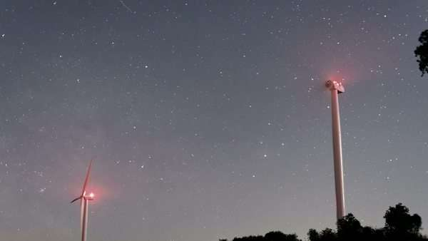 Timelapse of starry sky and crescent moon illuminating wind turbines. The Milky Way and Jupiter are clearly visible as well as many satellites Rights-managed stock video