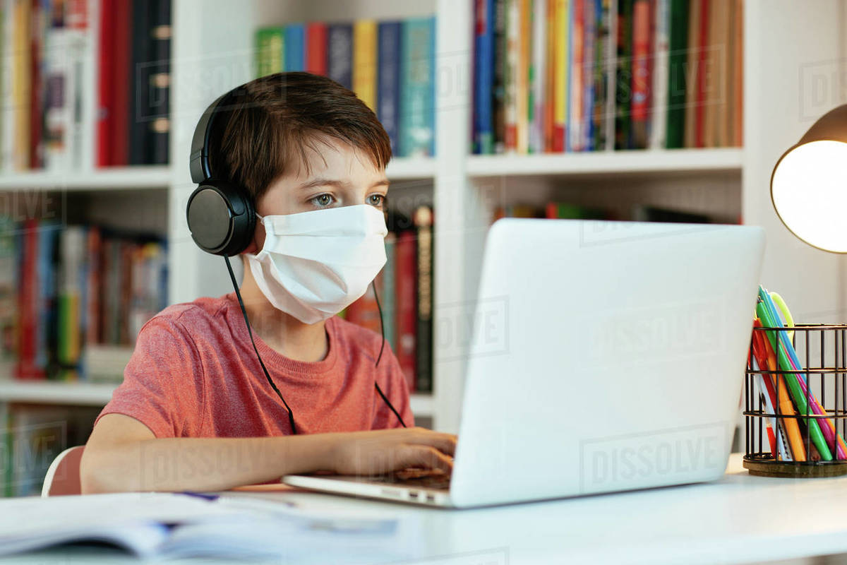 Child wearing face mask learning at home. Young student wearing surgical mask doing his homework on computer. Royalty-free stock photo