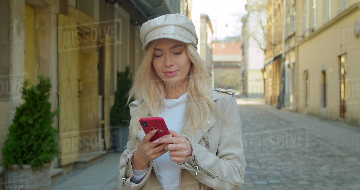 Attractive young woman using phone while walking in the city center. Chatting with friends, girl using cellphone outdoors. slow motion Royalty-free stock photo