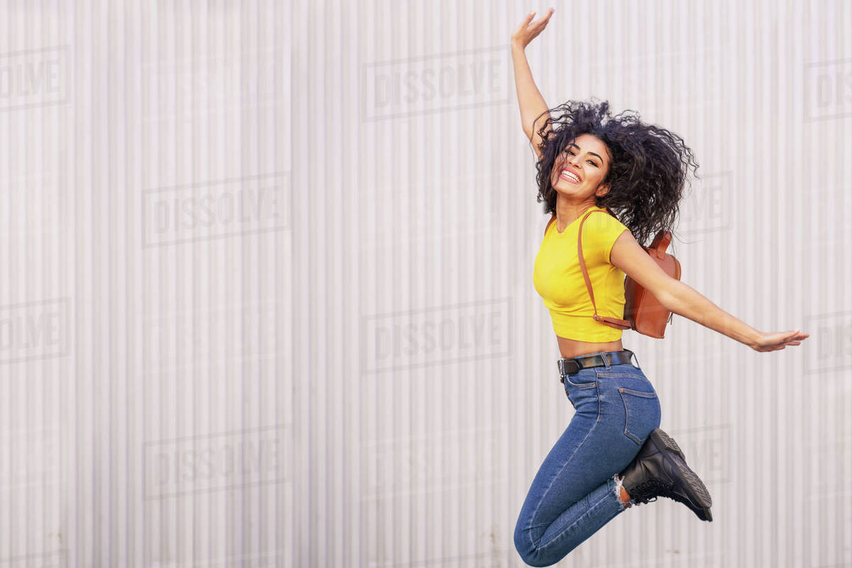 Happy woman jumping in urban background. Royalty-free stock photo
