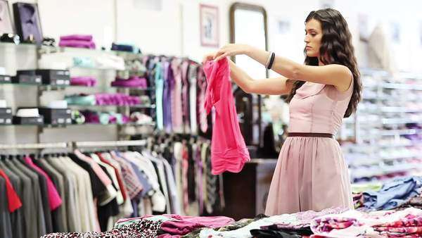 Young woman choosing and buying clothes at a boutique. Royalty-free stock video