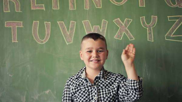 Portrait of a Smiling Caucasian Schoolboy Waving His Hand Royalty-free stock video