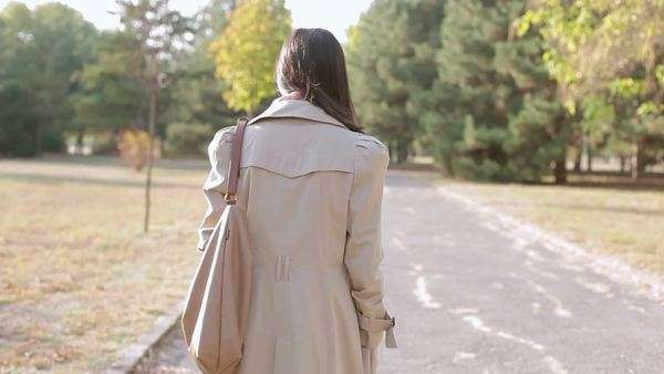 Back view of a young woman wearing a trench coat having a walk in a park. Royalty-free stock video