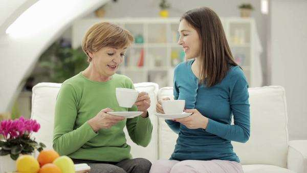 Elderly lady having a chat with her daughter over a cup of coffee. Royalty-free stock video