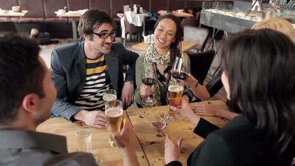 Multiethnic group of friends drinking beer and wine and having fun together. Royalty-free stock video