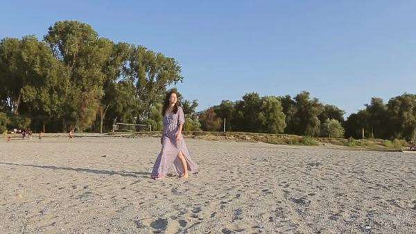 Woman in a long pink dress walking along a sandy beach. Royalty-free stock video