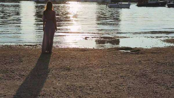 Young woman standing by a river at sunset. Royalty-free stock video