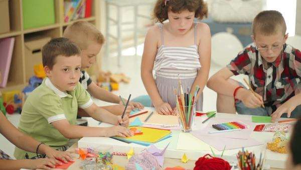 Group of cheerful preschoolers drawing together at the kindergarten. Royalty-free stock video
