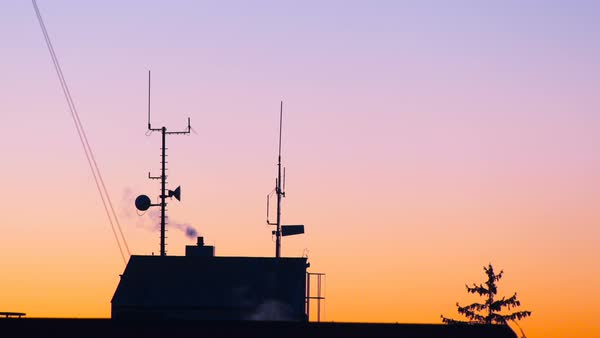 Silhouette of building roof with antennas and chimneys at sunset Royalty-free stock video