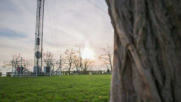 Behind the tree showing park with antenna and sunset. Wide shot panning from behind the tree to green lawn with antenna tower and sunset in background Royalty-free stock video