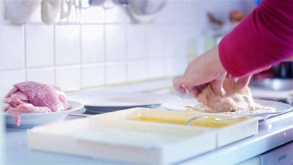 Woman in kitchen preparing lunch, making Wiener Schnitzel with meat marinade and ingredients. Royalty-free stock video