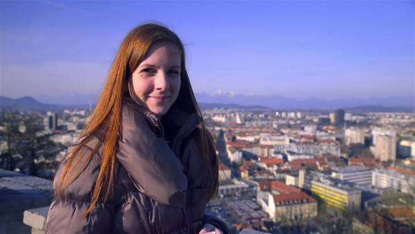 Confident woman looking in to camera above city scape. Female person with long brown hair looking in camera smiling, big city in background. Sunny day. Royalty-free stock video