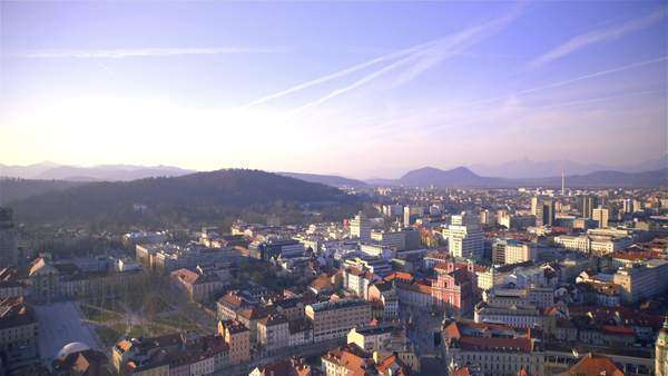 Panning Ljubljana city scape from castle tower. Top view of Ljubljana city buildings roofs panoramic shot before sunset. Royalty-free stock video
