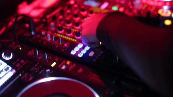 Handheld shot of a DJ mixing music on a sound desk Rights-managed stock video