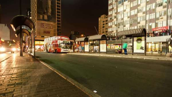 Static timelapse at night of a bus station in Ghandi Square in the city centre of Johannesburg, South Africa Royalty-free stock video