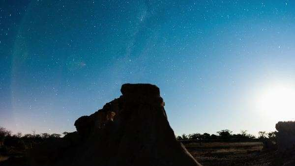 Linear, push-in night timelapse of abstract landscape with silhouette eroded rocks while the moon is setting and the Milky Way moves into the frame Royalty-free stock video