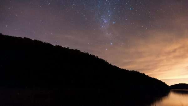 Linear and pan timelapse at night of a silhouetted mountain and a dam with the Milky Way and a dramatic thunderstorm Royalty-free stock video