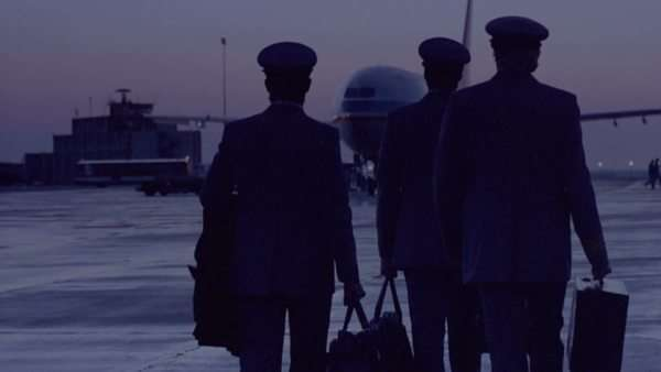 rear view of silhouetted pilots with briefcases walk towards parked airplane on runway Rights-managed stock video