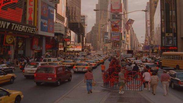 Extreme long shot, high angle over Times Square in New York, linear perspective down street over busy traffic and people trying to cross the road. Rights-managed stock video