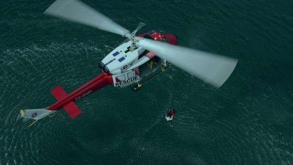 Aerial of two men being airlifted out of the sea by a rescue helicopter Rights-managed stock video