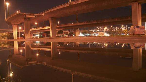 Time lapsed long shot under highway reflected in water, cars driving Rights-managed stock video