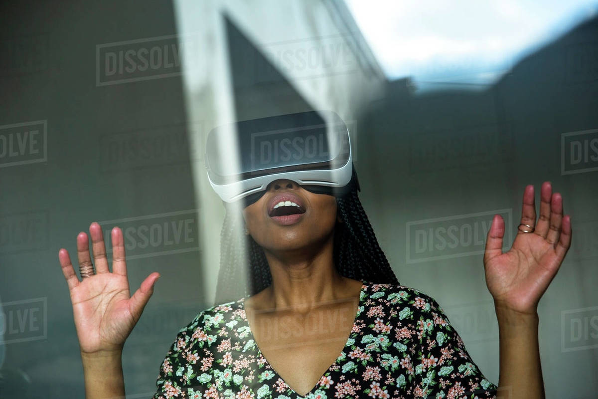 African woman looking through VR headset stock photo