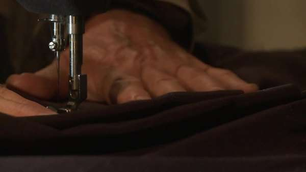 A close up of a man sewing fabric using a sewing machine Rights-managed stock video