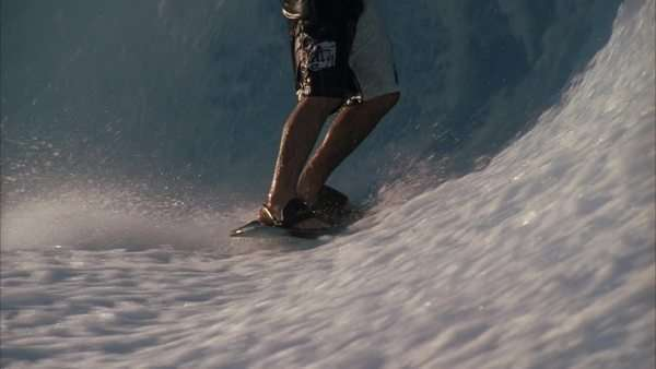 Slow motion, close up of a surfers legs riding a wave made from a wave machine Rights-managed stock video