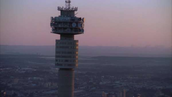 Aerial shot of the Hillbrow Tower towering above the Johannesburg Central Business District and passing the Ponte Tower during sunset/sunrise Rights-managed stock video
