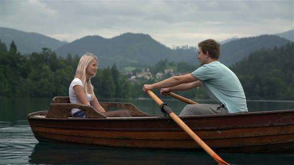 Romantic couple on boat rowing in slow motion. Boy and girl in love having a tour on lake, female admiring her lover. Royalty-free stock video