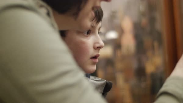 Hand-held shot of a mother and her son looking at a store display Royalty-free stock video