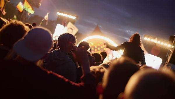 Crowd enjoying themselves at outdoor music festival. Slow motion of hands and girl in the air Royalty-free stock video