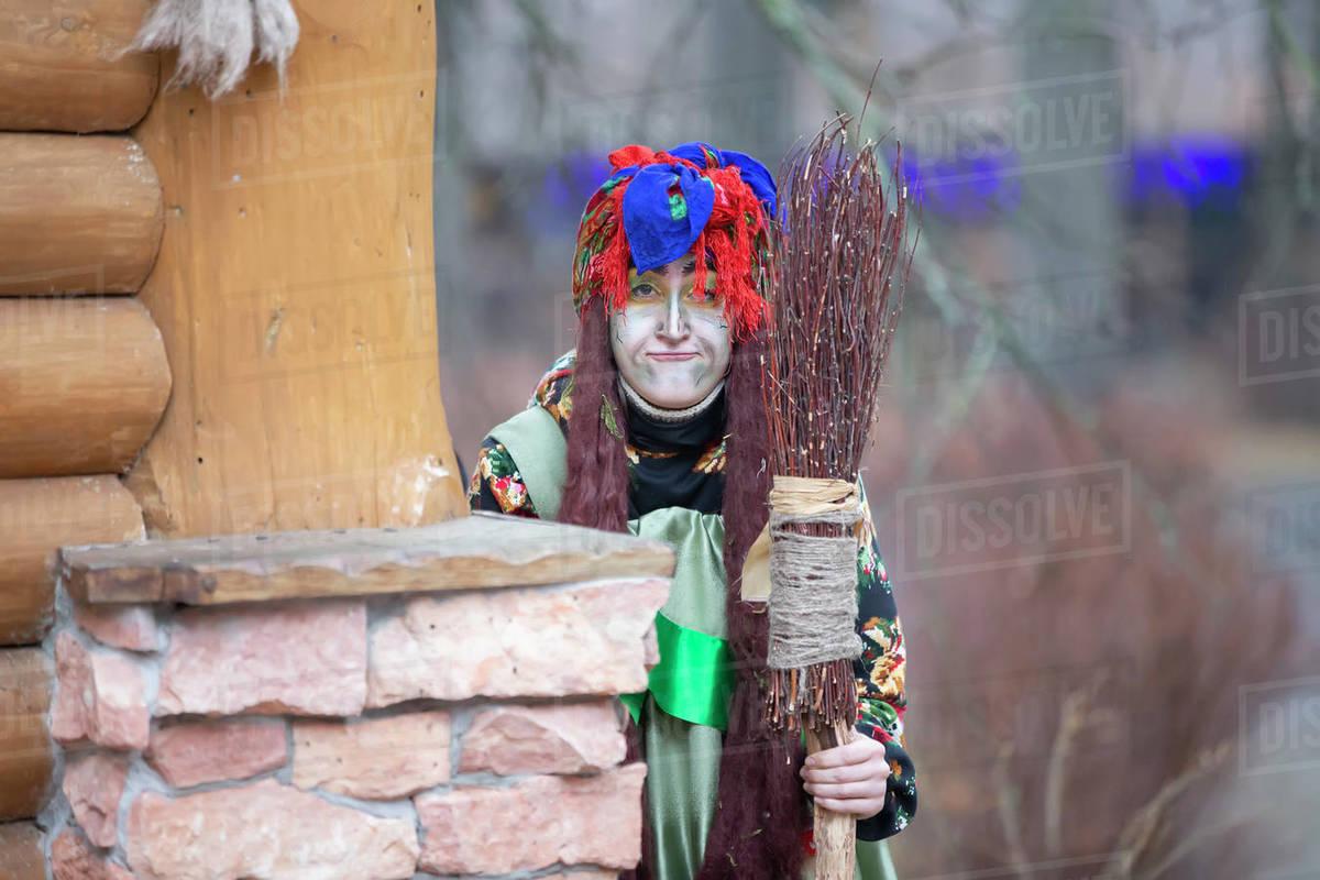 Baba Yaga with a broom near a wooden hut. Royalty-free stock photo