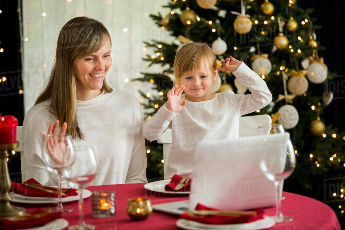 A happy family with a child is celebrating Christmas with their friends on video call using webcam.  Royalty-free stock photo