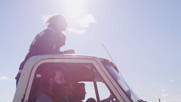 A couple stands in the bed of a pickup truck as it drives along a rural road Royalty-free stock video