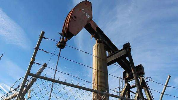An oil derrick pumps oil Royalty-free stock video