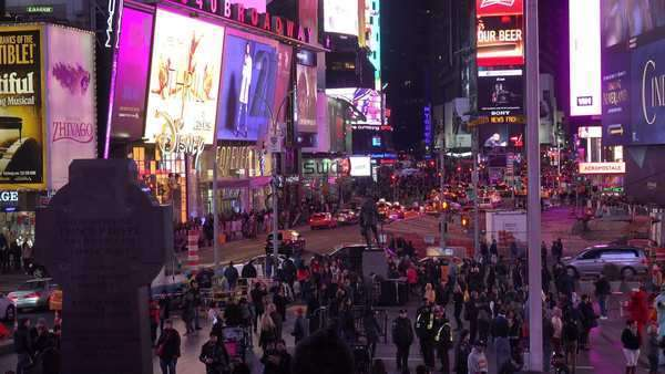 Nighttime crowds of people and bright neon advertisements in Times Square, New York City. Royalty-free stock video