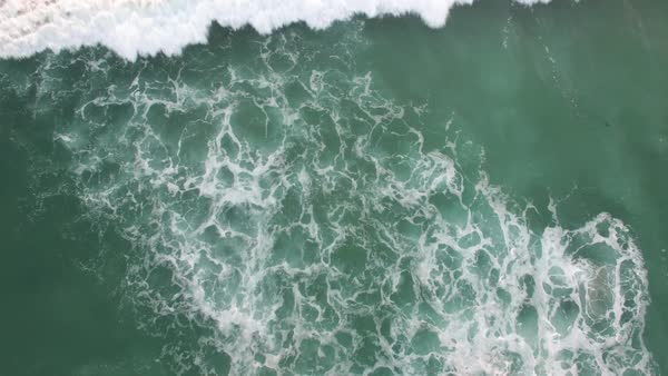 A rising aerial perspective looking straight down at the ocean with waves rolling in. Royalty-free stock video