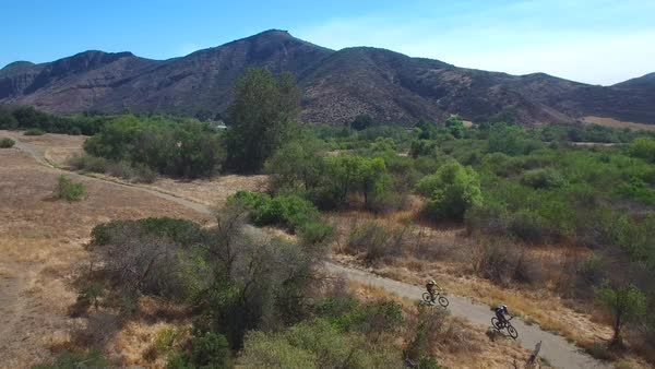 Good aerial following two mountain bikers riding in the California mountains. Royalty-free stock video